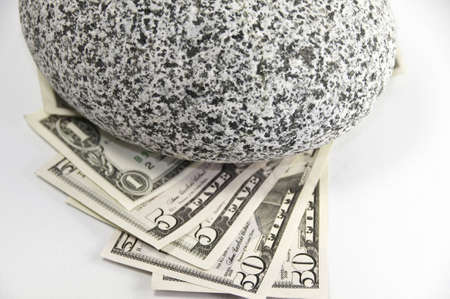 American 1,5,50 dollars bills held down by a round granite rock. Stock Photo - 5340330