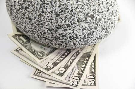 American 1,5,50 dollars bills held down by a round granite rock. Stock Photo - 5340330