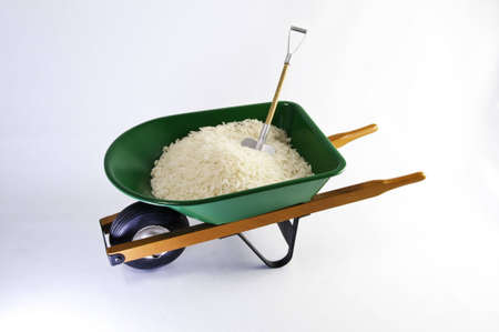 wheel barrel: Rice ic in a green wheel barrel with shovel.It is on a white background.