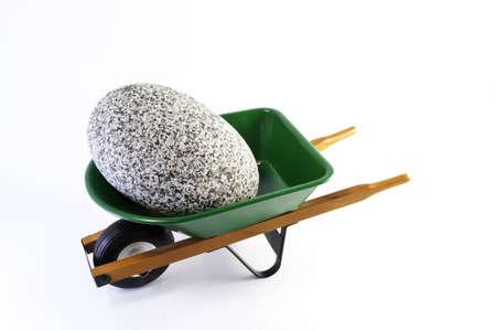 wheel barrel: Large rock in wheel barrel.It is on a white background.