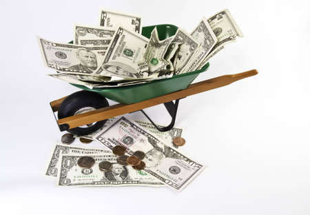 American dollars filling a green wheel barrel with more money under it. View from top.White background.
