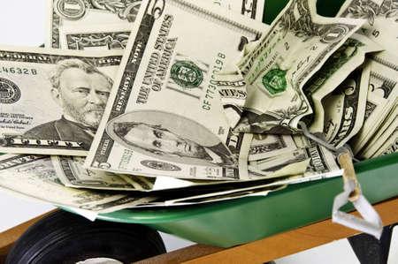 wheel barrel: Close up of american dollars in a green wheel barrel.