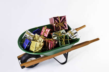 Top view of Christmas presents in a green wheel barrel.It is on a white background. view of Christmas presents in a green wheel barrel.It is on a white background.