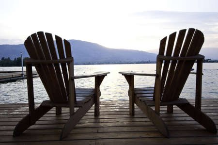 comfortable chair: Two lounge chairs on a deck by the lake in the setting sun. Stock Photo