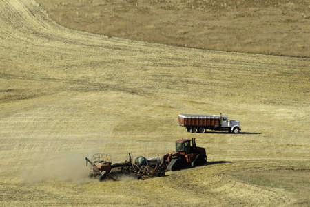 colfax: Farmer working the field with tractor. He is tilling and spraying the field in one go around.