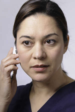 Women hold the telephone and she is closly listening to the conversation. Stock Photo