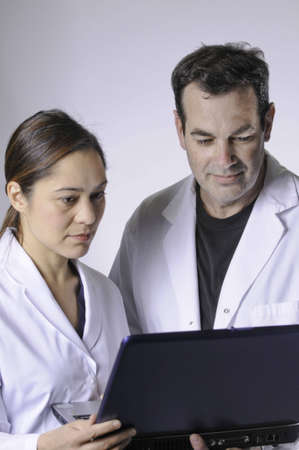Two medical people looking at the laptop.Women is mixed race young lady.