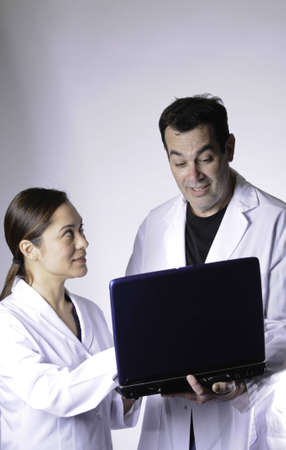 Female and male medical persons looking at the computor.The young lady is mixed race.