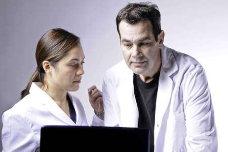 Dos personas médicas mirando la laptop.Women es la Dama de yuoung de raza mixta. Foto de archivo - 6503237