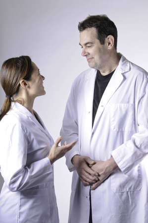 A mixed race young lady talking with a man. They are wearing lab coats.