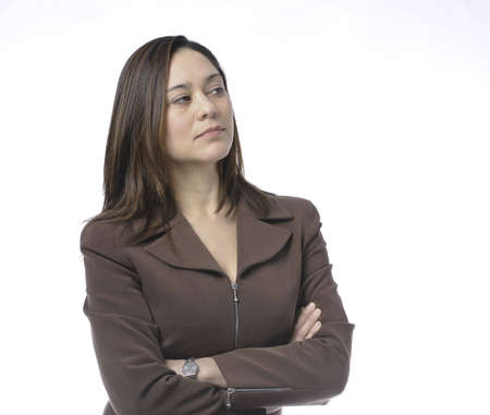 Young women has her arms crossed.She is of mixed race.Wearing a brown suit and has long brown hair.Her head is turn sideways.It is on a white background Stock Photo