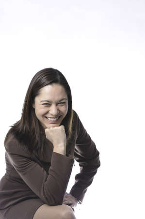 Young lady of filipino ethnicity,is sitting on stool with a white background.
