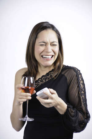 Young woman crying and has a glasss of wine in her hand along with a telephone. She is of mixed ethnicity.