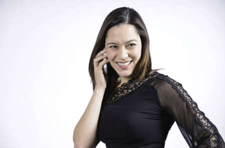 young woman talking on the telephone and is smiling. She is of mixed ethnicity. Stock Photo
