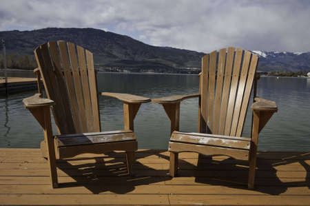 Two adirondack chairs on the dock. photo