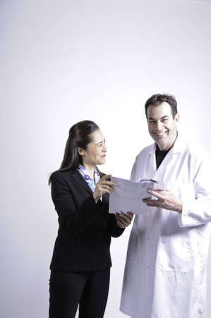 Two professional people looking at a sheet of paper.The young lady is of mixed race .The man is very happy.