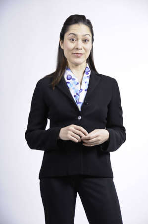 Young business woman has both hand crossed  She has her smirk on her face.  She is of mixed ethnicity.