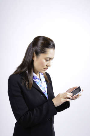 A mixed race woman looking at the telephone. She is  wearing a black suit ,she has long brown hair.