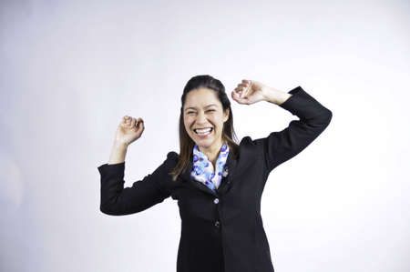 Young business woman has both arms in the air. She has a large smile  She is of filipino ethnicity. Stock Photo