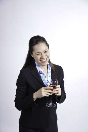 A young business woman holding a glass of wine.She is of filipino ethnicity.
