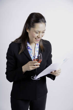 Business woman reading and has a glass of wine in her hand.She is of mix race.