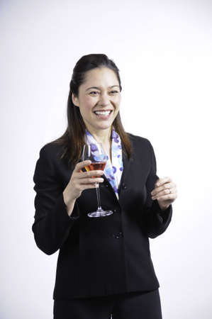 Young business woman holding a glass of wine in her hand, Wearing a black  suit this young woman  is of filipino ethnicity.