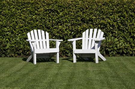Witte adirondack stoelen op een gazon witte een hedge-bachground.