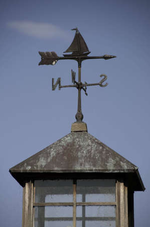 Weather vane on a roof top.It has a lookout. Stock Photo