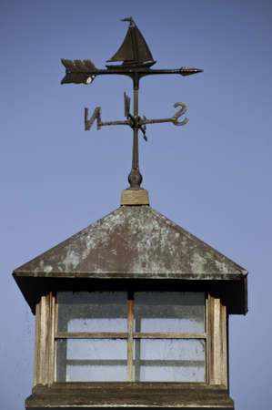 Weather vane on a roof top.It has a lookout on top.