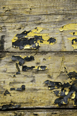 Wooden planks with paint that has dried and is blistered.