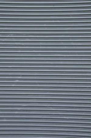 Grey horizontal freight door . It is a roll up grid style door.. Stock Photo