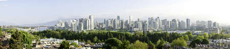 Panoramic water view of dowtown highrise area of  Vancouver , British Columbia,Canada fronted by a park and shorline of False Creek. There is a light early morning mist.