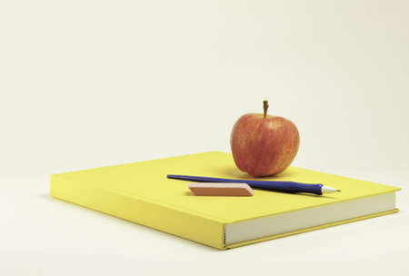 Yellow school book with pen eraser and apple on top of cover.This has clipping mask
