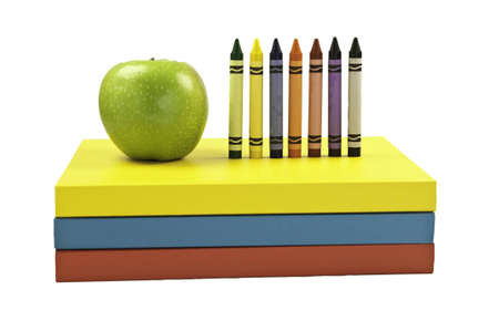 Green apple along side colored crayon on top of three books. This has a clipping path.