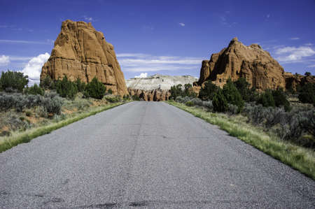 Two large  hills of rock framing the roadway  Light fluffy clouds in the sky