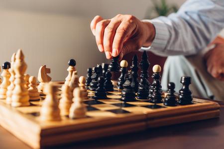 経験豊富なチェス プレーヤーの手でポーンをブラック