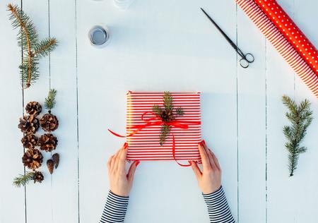 dar un regalo: Presente envuelto en papel rojo sobre un fondo de madera con una cinta roja para la Navidad, cumpleaños, día de San Valentín o de la madre
