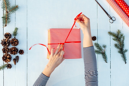Gift wrapping. Woman packing gifts, step by step