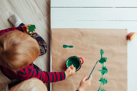 child drawing: Children drawing a Christmas tree on classic paper