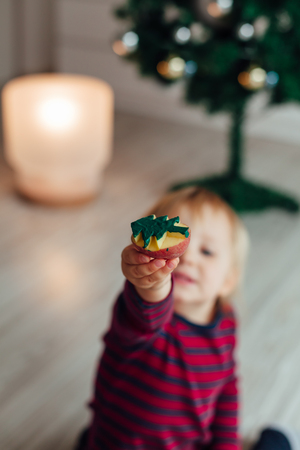 potato tree: Little girl holding colored Christmas tree made from potato. Copy space.