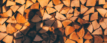 outdoor fireplace: Pile of cut wood with photographer shadow at sunset, copy space