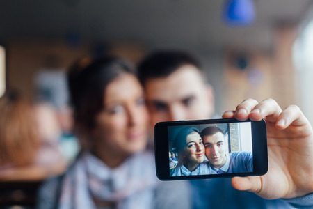 young couple: Young couple in love taking photos of themselves in a cafe