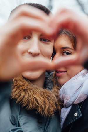 finger teen: Closeup of couple making heart shape with hands
