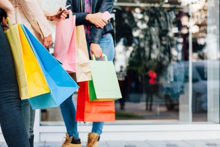chicas de compras: Muchachas con los regalos que se colocan delante de las ventanas de compras