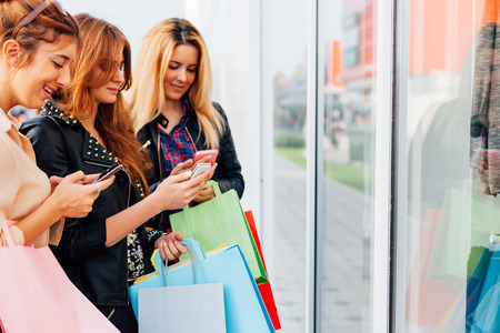Three girls with colorful shopping bags using smart phones with copy space