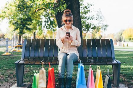 comprando: ni�a feliz con tel�fono inteligente despu�s de las compras navide�as Foto de archivo