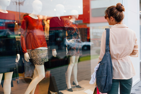 Happy girl looking in a shop window