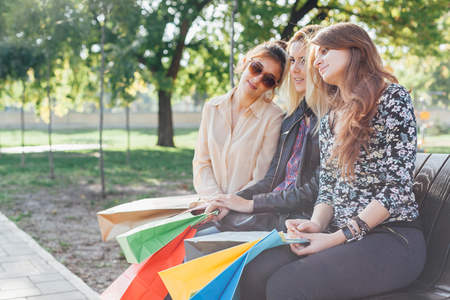 after shopping: Three beautiful girls resting in the park after shopping