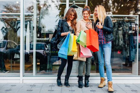 shopwindow: Girls with shopping bags are satisfied with the purchase Stock Photo