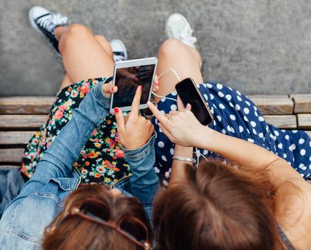 携帯電話とタブレットを使用して 10 代の少女のオーバー ヘッド ビュー